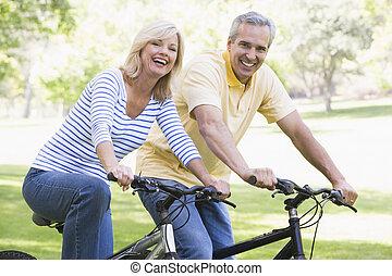 pareja, en, bicicletas, aire libre, sonriente