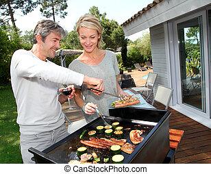 pareja, en, jardín, cocina, carne, en, barbacoa