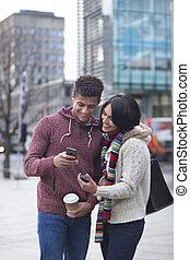 pareja, en la ciudad, el mirar, un, smartphone