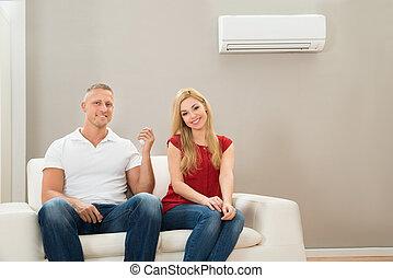 pareja, en, sofá, utilizar, acondicionador de aire
