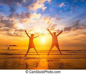 pareja, enamorado, saltar, en, el, océano, playa, durante, asombroso, ocaso, ., long-awaited, vacaciones, concepto, y, romántico, honeymoon.