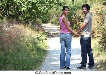 pareja fuera, ambulante, tomados de la mano