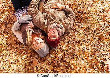 pareja joven, acostado, en, otoño sale