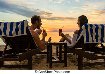 pareja joven, bebida, cócteles, en, un, playa, en, ocaso, durante, vacaciones
