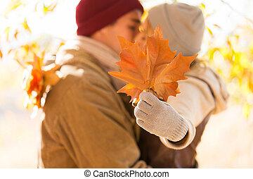 pareja joven, besar, atrás, otoño sale