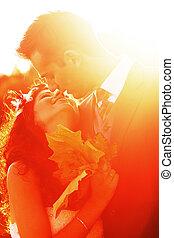 pareja joven, besar, en, brillante, ocaso