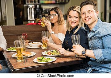 pareja joven, comer afuera, con, amigos