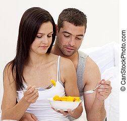 pareja joven, comida, fruta, en cama