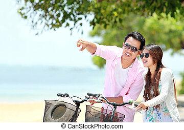pareja joven, con, bicicleta, en la playa