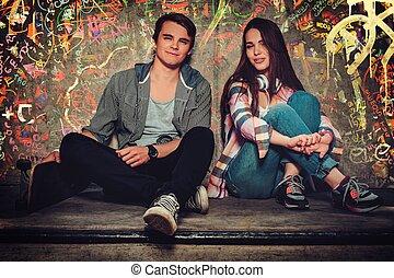 pareja joven, con, monopatín, aire libre, contra, grafiti, pared pintada
