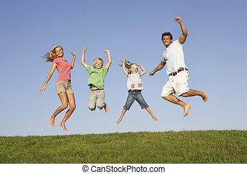 pareja joven, con, niños, saltar en, un, campo