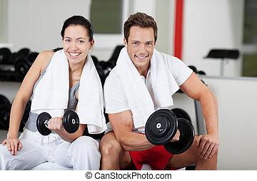 pareja joven, elevación, dumbbells, en, gimnasio
