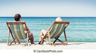 pareja joven, en, sillas de playa