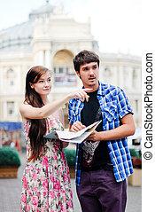 pareja joven, hombre y mujer, mirar, mapa, en, ciudad, centro, y, actuación, dirección
