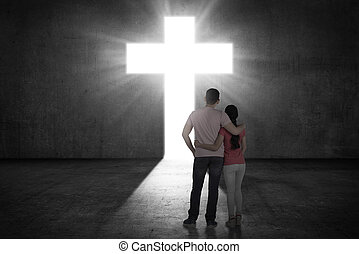 pareja joven, mirar, el, brillar, cruz, en, la pared
