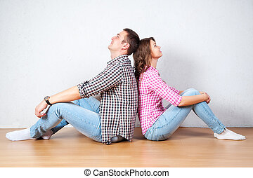 pareja joven, relajante, sobre el piso, en casa, sentado, descalzo, de nuevo a la parte posteriora, cada, mirar hacia arriba, en, el, aire, con, un, pensativo, sonrisa, como, ellos, plan, su, futuro, juntos