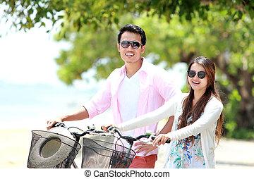 pareja joven, retrato, con, bicicleta, en la playa