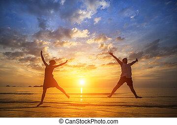 pareja joven, saltar, en, el, océano, lado, durante, asombroso, sunset., long-awaited, vacaciones, concept.