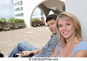 pareja joven, sentado, en, campus, yarda