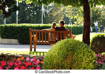 pareja joven, sentado, en, un, banco, en el parque