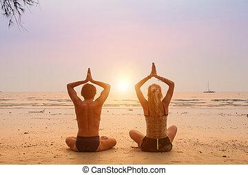 pareja joven, sentado on the beach, de, el, mar, en, el, posición lotus, en, sunset.