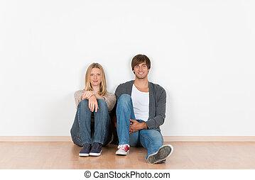 pareja joven, sentado sobre el piso