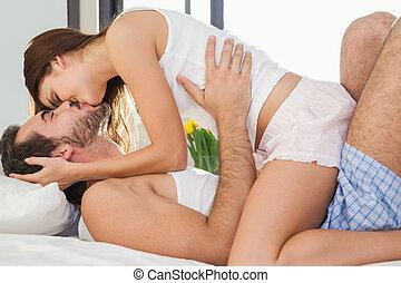 pareja joven, tener diversión, en cama