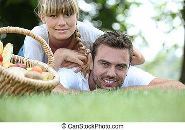 pareja joven, tener un picnic, en el parque