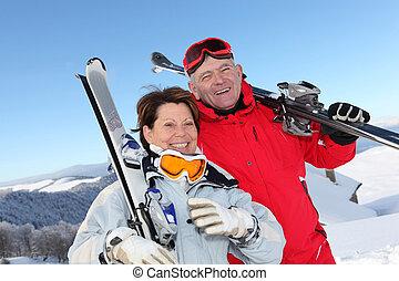 pareja jubilada, viaje, esquí, diversión, teniendo