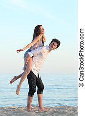 pareja, juego, a cuestas, en la playa