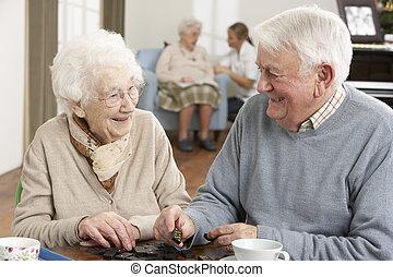 pareja, jugando dominós, en, cuidado día, centro