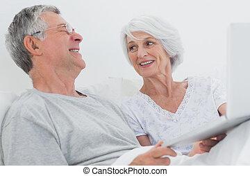pareja, juntos, alegre, maduro, usar la computadora portátil