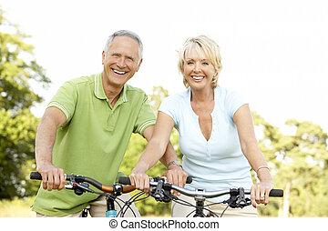 pareja madura, bicicletas de equitación
