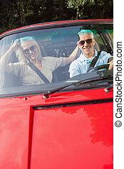 pareja madura, en, rojo, cabriolet, sonriente, en cámara del juez