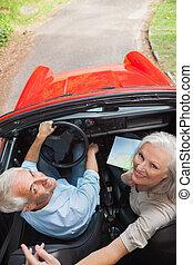 pareja madura, en, rojo, convertible, mirar cámara del juez