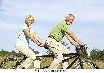 pareja madura, equitación, tándem