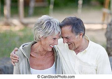 pareja mayor, con, cabeza dirigir, sonriente, en el estacionamiento