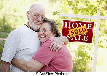pareja mayor, delante de, vendido, signo bienes raíces