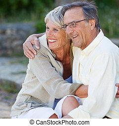pareja mayor, el mirar lejos, mientras, se abrazar, en el estacionamiento