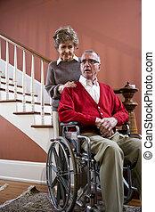 pareja mayor, en casa, hombre, en, sílla de ruedas