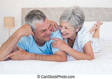 pareja mayor, juntos, cama, sonriente