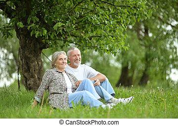 pareja mayor, sentado, aire libre