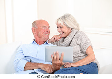 pareja mayor, utilizar, electrónico, tableta, en casa