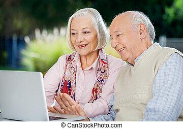 pareja mayor, vídeo, charlar, en, computador portatil