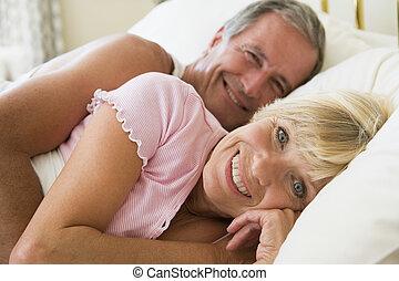pareja, mentira en cama, sonriente