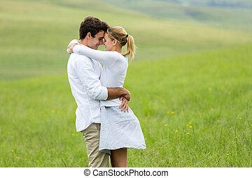pareja que se abraza, joven, aire libre