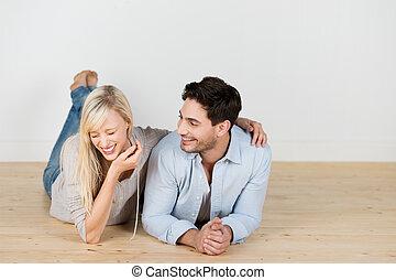pareja, reír, joven, acostado, piso