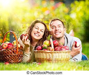 pareja, relajante, en la hierba, y, comida, manzanas, en, otoño, jardín