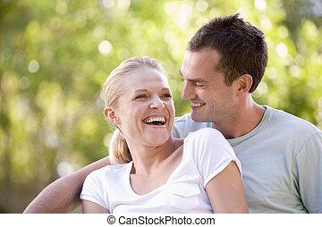 pareja, sentado, aire libre, reír