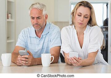 pareja, texting, aburrido, mostrador, sentado